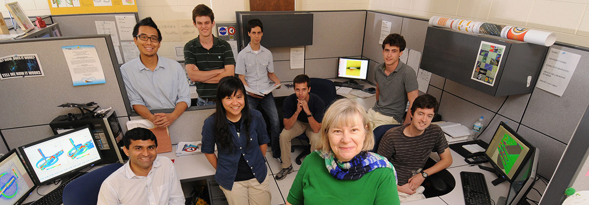Dr. Marilyn Smith with a group of 8 students in an office.