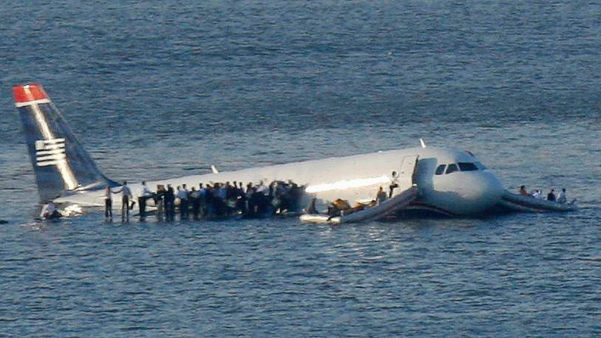 Plane in the Hudson River with passengers standing on the wings